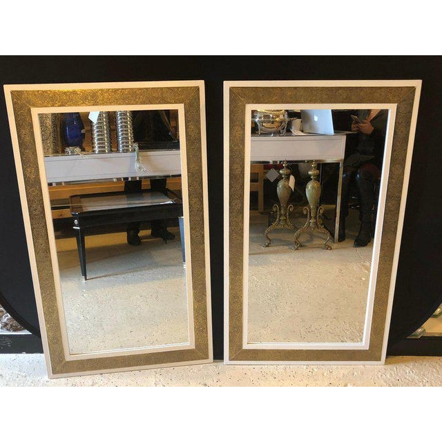 A pair of elegant brass on white wood framed console or pier mirror. The brass frame features handcrafted opulent design....