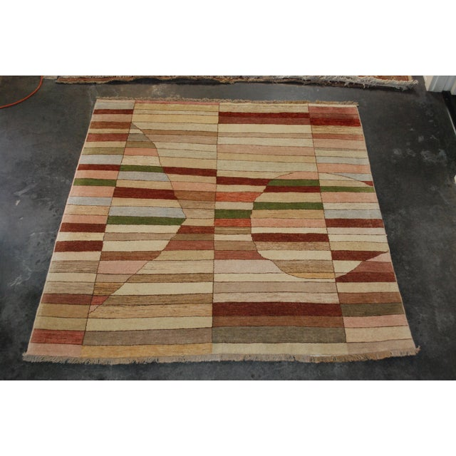 A square asymmetrical-patterned rug in hand-knotted wool.