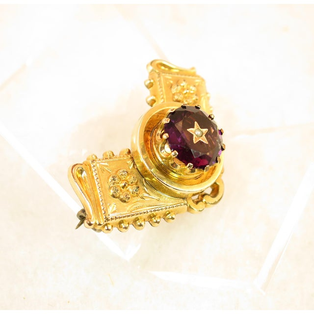 Offered here is a Georgian solid 10K gold brooch with a carved amethyst, Circa 1830. This diminutive V-shaped brooch is...