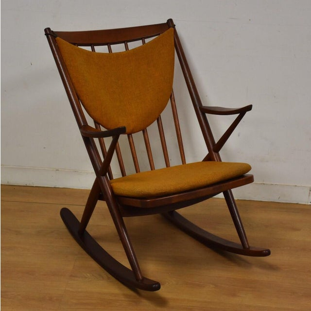 A mid century modern oiled teak rocking chair designed by Frank Reenskaug for Bramin with new straps and orange cushions....