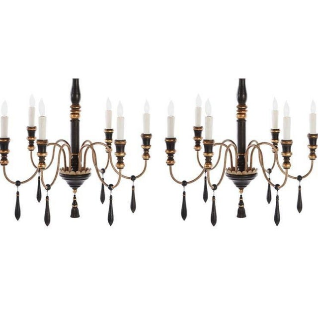 One pair of regency style six-arm chandeliers with ebonized finish, gilt highlights.