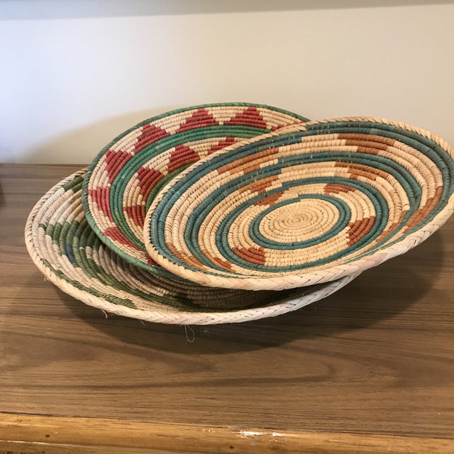 """Trio (3) of beautiful flat woven rattan African baskets. Dimensions: Small Basket (2): 13"""" X 2 1/4"""" Large Basket (1): 15""""..."""