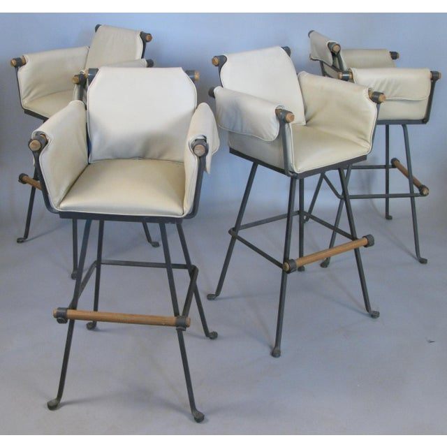 A beautiful set of four vintage 1970s Cleo Baldon for Terra Furniture swivel barstools with wrought iron frames and oak...