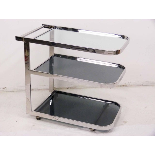 Circa 1980s streamlined Art Deco three tier chrome flat bar tea cart in the manner of Milo Baughman and Pace. The cart...