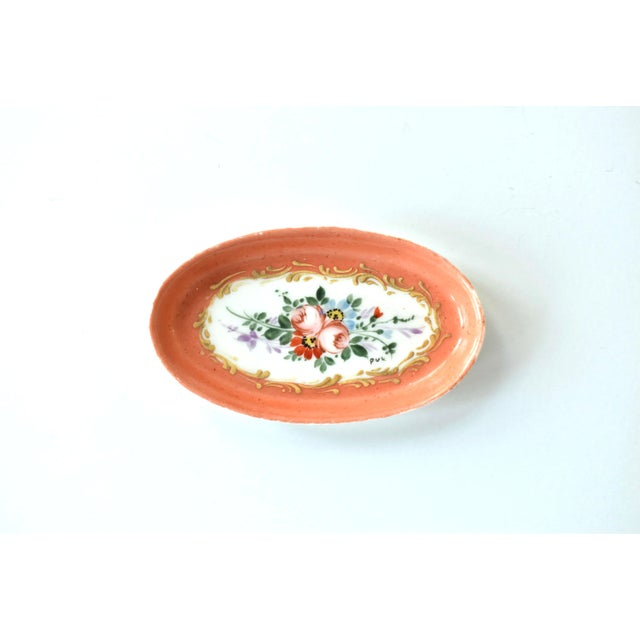 An antique 19th-century hand-painted oval ring dish, pin dish, or trinket dish, in a delicate orange or deep coral, with...