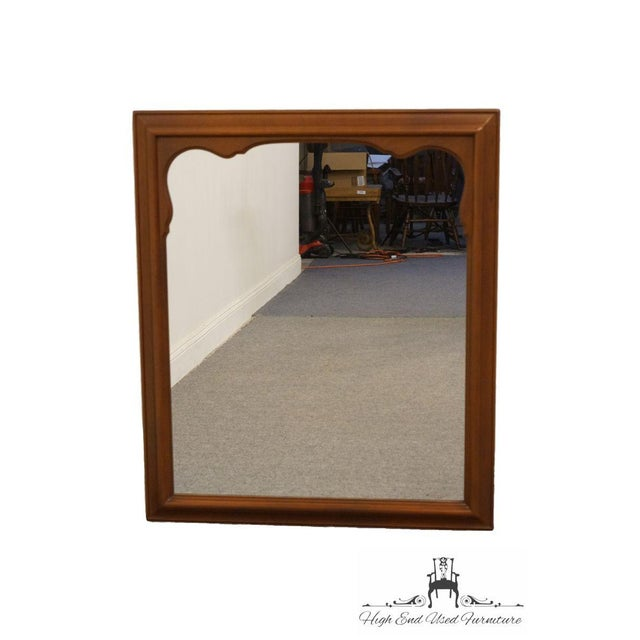 This is a vintage wall mirror by Kindel Furniture. The piece is from the late 20th century and made of fruitwood.