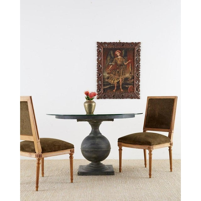 Attractive neoclassical style pedestal dining table or center table. Features a vasiform design pedestal wrapped in metal...