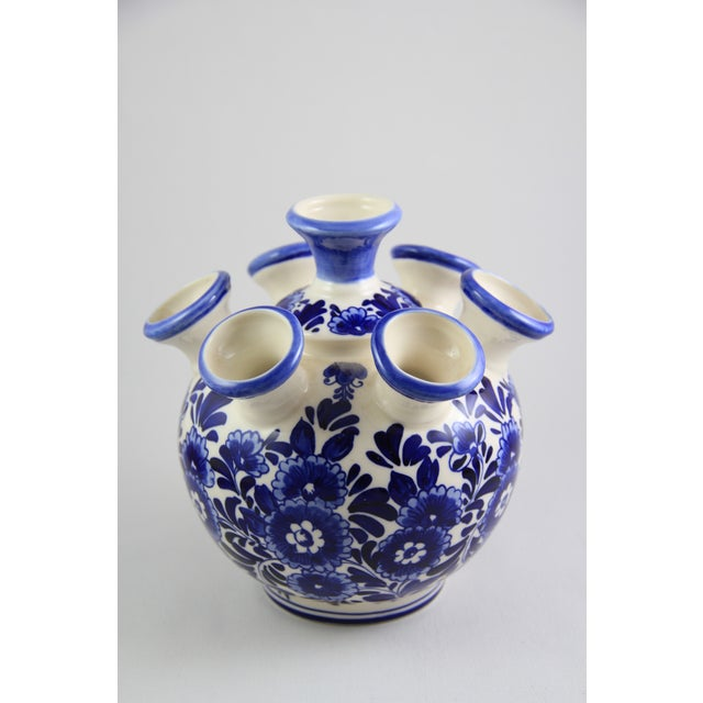 A beautiful, hand-painted porcelain vase in blue and white. Marks on the bottom. Features seven vase openings.