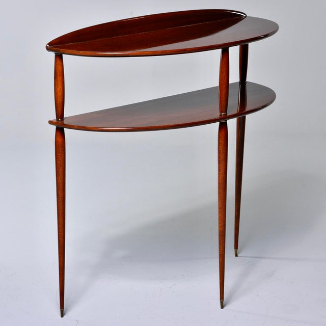 Two-tier palisander console features a demilune shaped tabletop and lower shelf and slender, tapered legs with brass-...