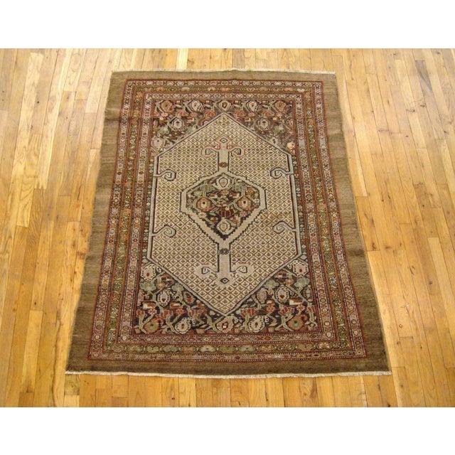 "An antique Persian Hamadan camel hair oriental rug, circa 1910, size 5'2"" x 3'9"". This delightful small carpet features a..."
