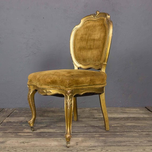 Pair of French 19th century giltwood side chairs with distressed brown upholstery. The gilding is original and shows a...