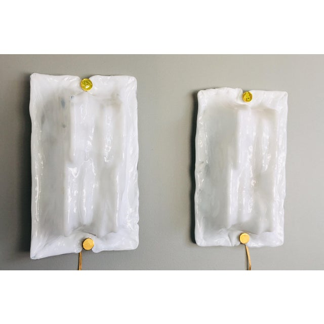 Pair of modernist white glass sconces by Toni Zuccheri for Venini. The sconces are rectangular with brass fasteners. They...