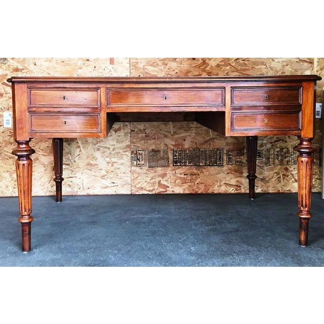 Antique five-drawer desk with a leather top and detailed turned legs.