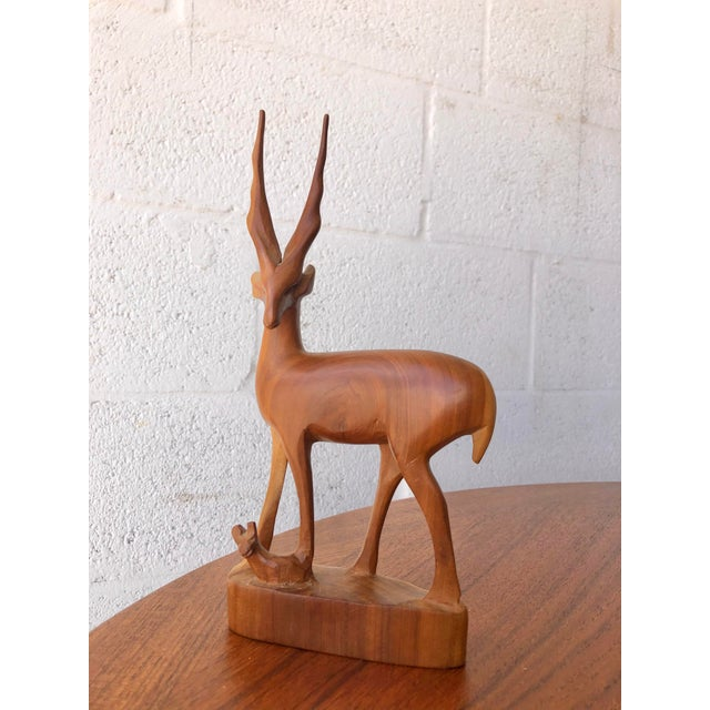 Vintage Mid Century Modern Hand Carved Wood Antelope Sculpture Features an antelope and a baby fawn hand-carved from a...