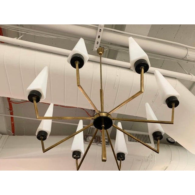 A striking 1960s brass 8-arm chandelier with rare white Prisma shaped shades by Oscar Torlasco for Lumi. Newly rewired.