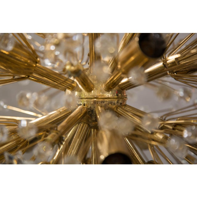 A chandelier by Emil Sterner featuring crystal flowers and gold details.
