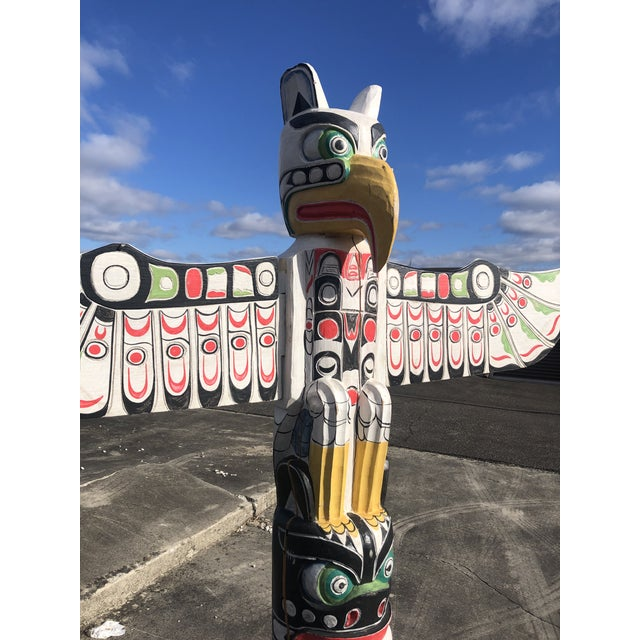 An eye catching hand carved tribal totem pole having bold color palette in black, red, green and white and yellow,...