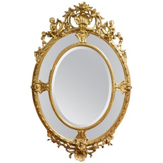 English 24-Karat Water Gilt Oval Mirror Adorned With Cherubs and Shells For Sale