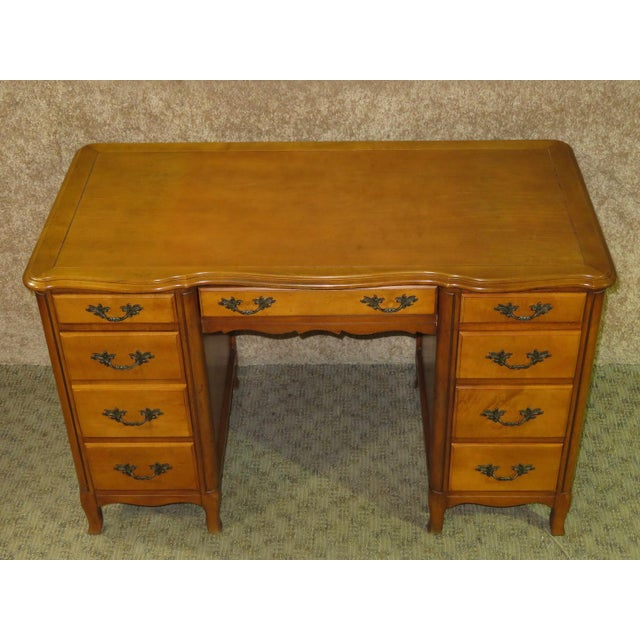 Knee hole desk with eight drawers has a French Provincial style. The desk is made of wood. The color a butternut finish....