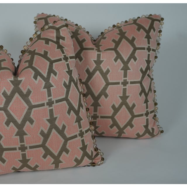 Designer indoor/outdoor pillows finished in textile by Kravet finished with decorative ball trim. 50/50 down & feather...