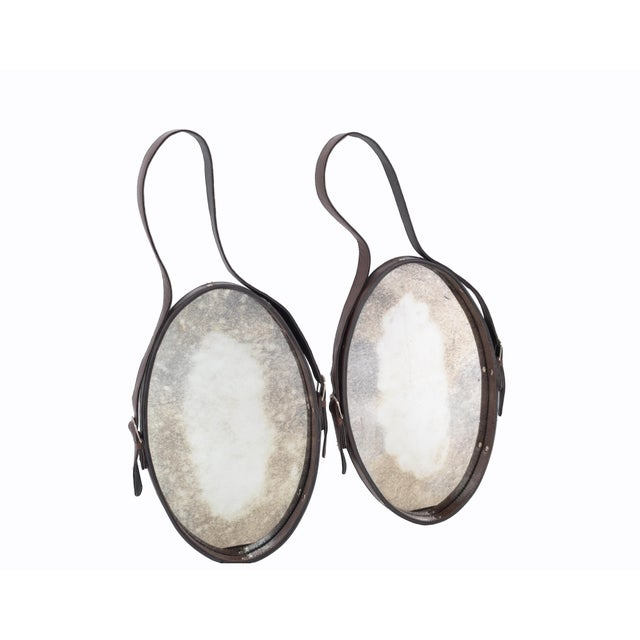 We offer a Pair of Oval Jacques Adnet hand-crafted brown Leather Wall Mirror with Antique Glass from the 1950s, made in...