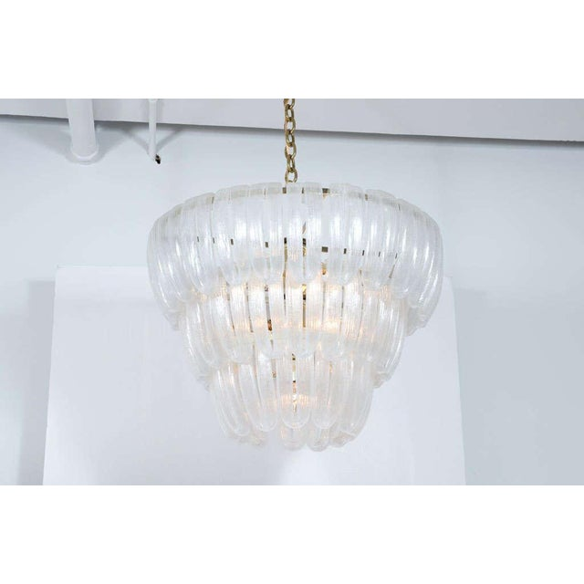 An elegant chandelier composed of hand blown glass loops suspended in three descending tiers of concentric circles from a...