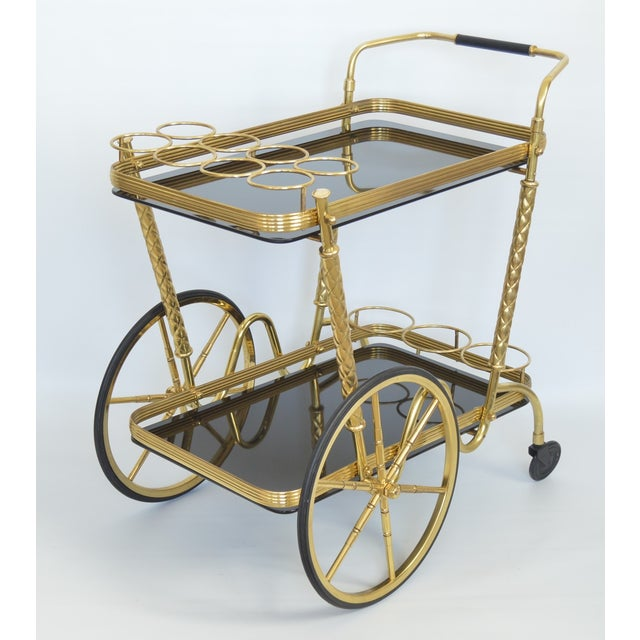 Exquisite Mid Century Italian brass and black glass bar cart, circa 1950's. This beautiful cart is made of solid brass...