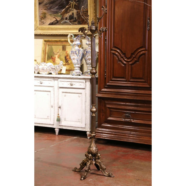 This gilt brass and metal hall tree was crafted in Italy, circa 1920. Standing on four legs with female figural busts...