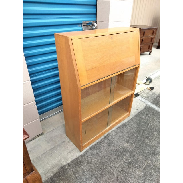 Mid century modern secretary desk/bookcase, drop down front opens to reveal small shelves and two small drawers, over two...