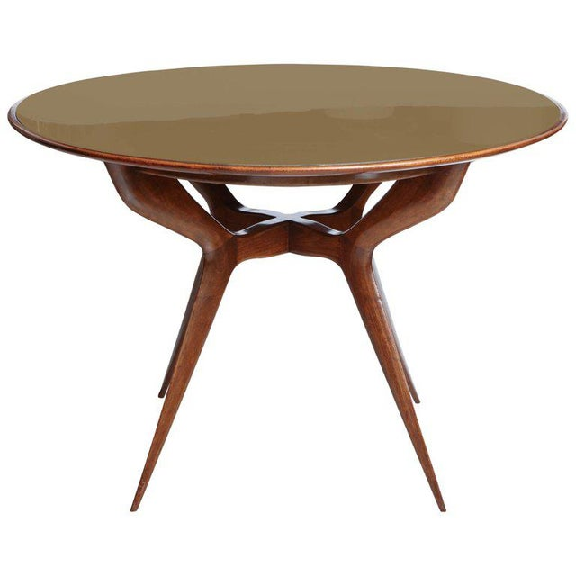 Italian Mid-Century Modern circular table with splayed wood legs and a reverse painted gold glass top, in the style of Ico...