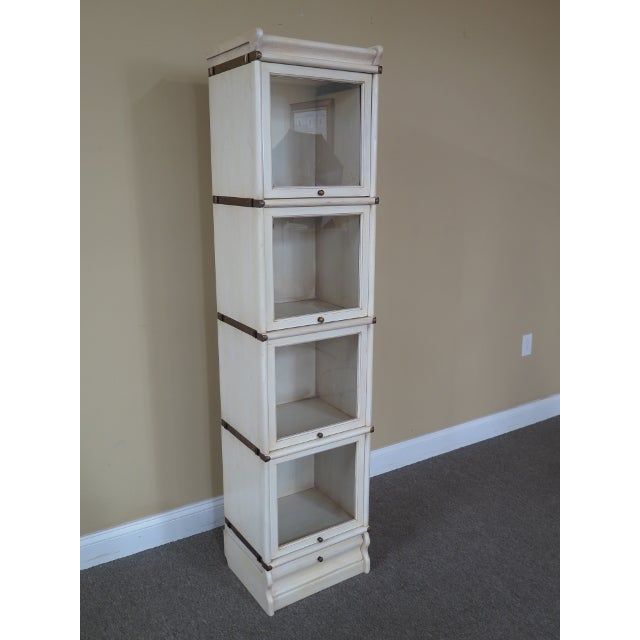 Globe Wernicke 4 section white stacking narrow bookcase. Features solid brass hardware, retractable doors, 1 drawer base...