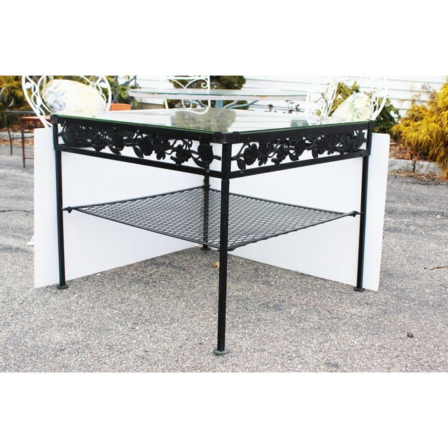 Square glass top iron outdoor table with mesh lower level and leaf decorations.