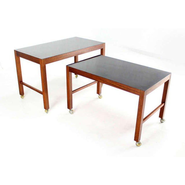 Very nice mid century modern walnut nesting tables with black laminated tops.