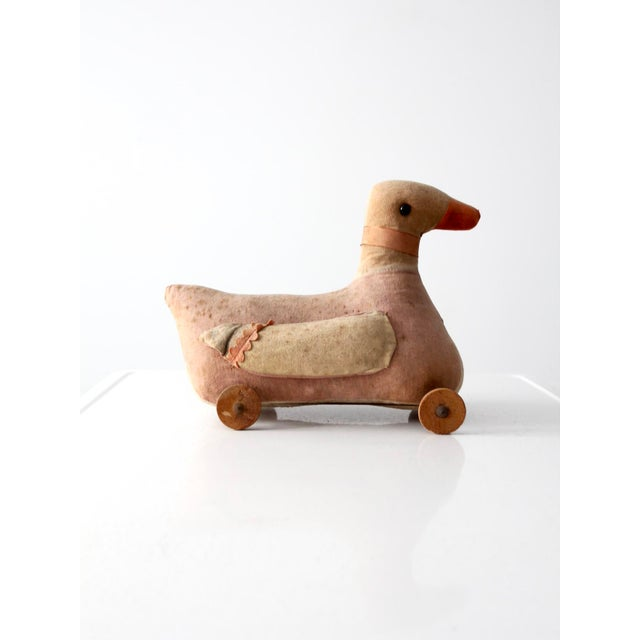 An early 20th century toy duck on wheels. The pink and beige fabric duck features bead eyes, a ribbon with bell around the...