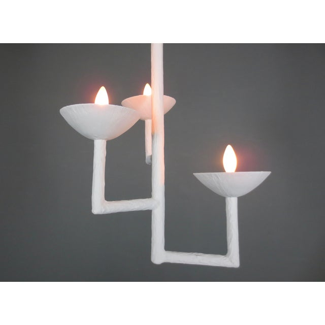 Three cup and light square chandelier with L-shaped extended arms. Plaster and steel multi armed chandelier with a white...