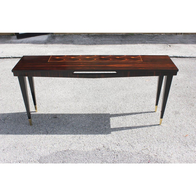 A beautiful French Art Deco exotic Macassar ebony steeped console table, circa 1940s. with Black lacquer legs ,and brass...