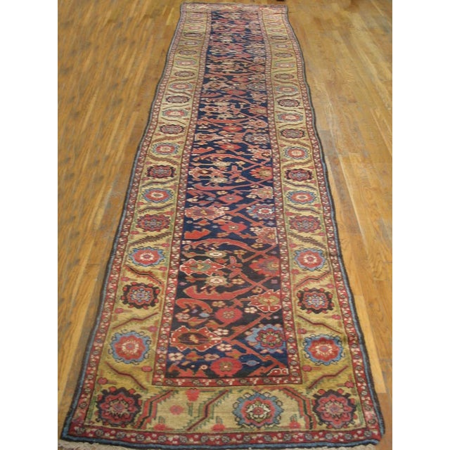 Antique NW Persian Rug with an ivory background and red border.