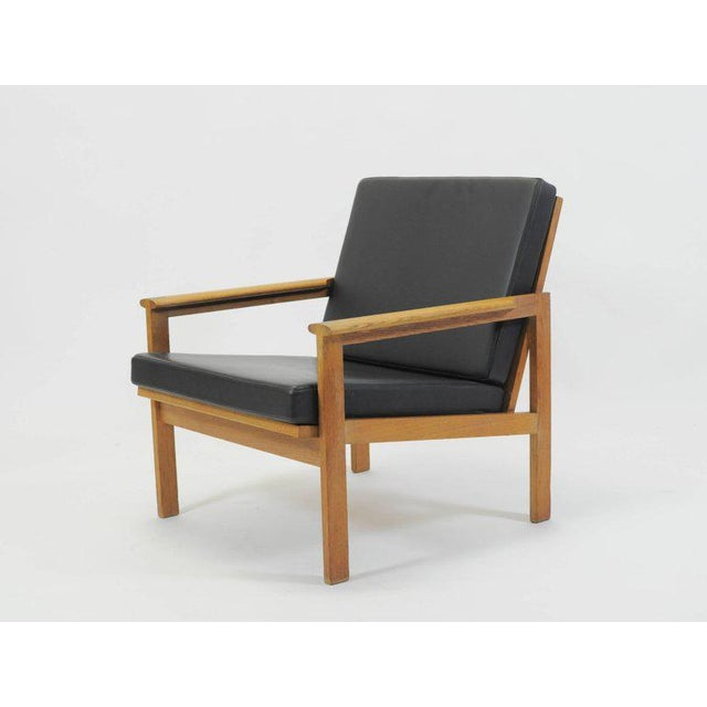 Danish Capella lounge chairs in oak with upholstery in black leather designed by Illum Wikkelsø in 1959 and produced by N....
