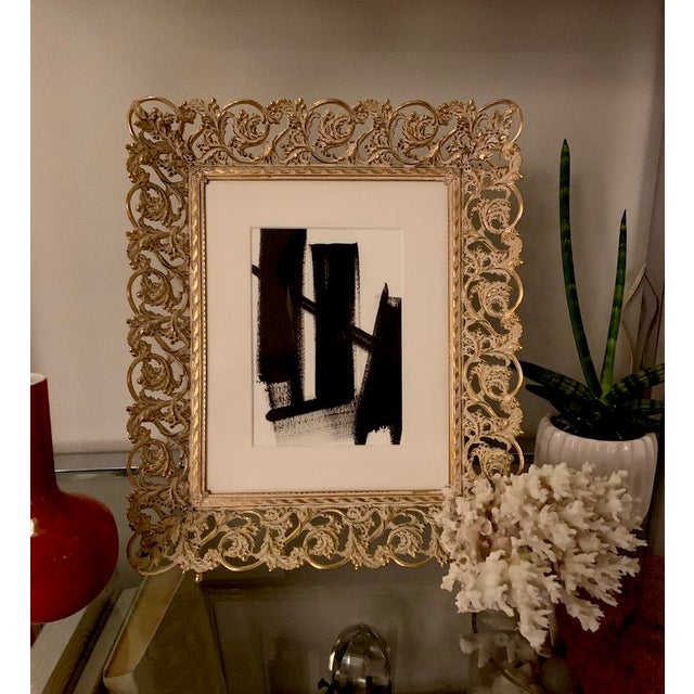 This beautiful black acrylic painting on paper is framed in a decorative gold metal frame. Can be hung on the wall or...