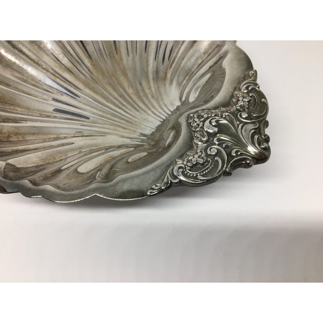 This ornate serving dish in the shape of a shell with three silver balls for feet is a nice wedding or shower gift. The...