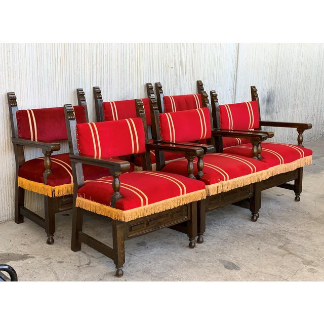 19th century set of six Spanish low armchairs in carved walnut and red velvet upholstery decorated with yellow fringes.