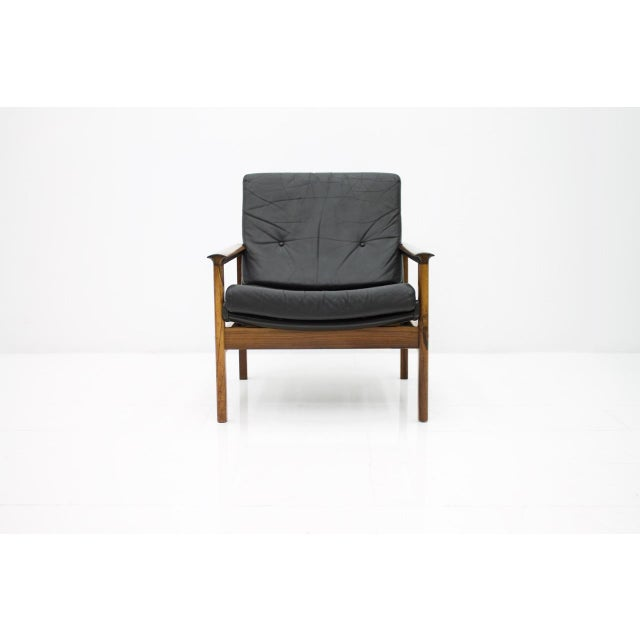 Scandinavian lounge chair in rosewood and black leather with loose cushions. The back of the armchair is also covered with...