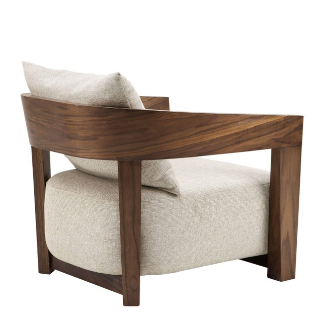 The Rubautelli Chair comprises a wooden frame with walnut veneer and features a Loki natural upholstery and cushion....