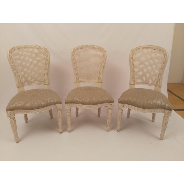Set of three French cane back chairs beautifully crafted and upholstered. Chair frame finished in white (not cream) with...