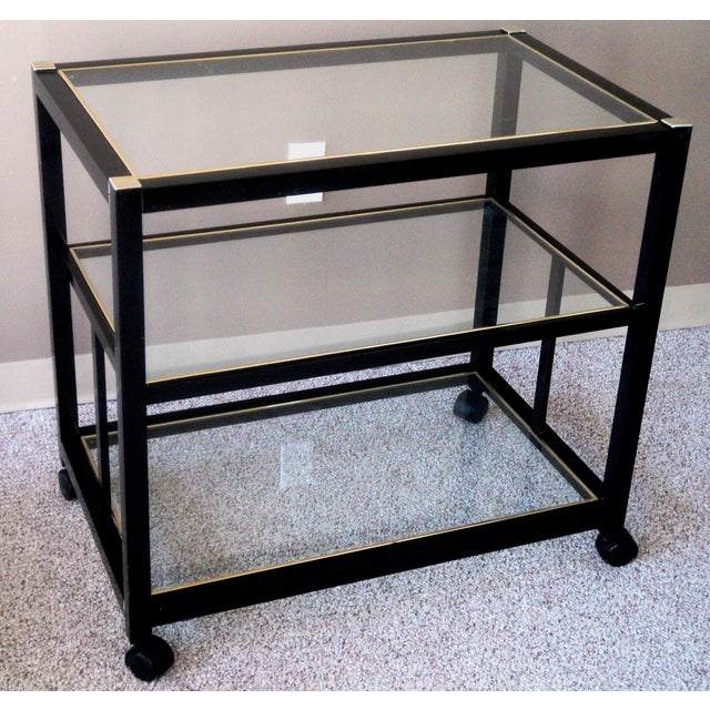 Sleek 1980s three tier black bar cart. Black powder coated metal structure. Original glass panes with gold tint foil...