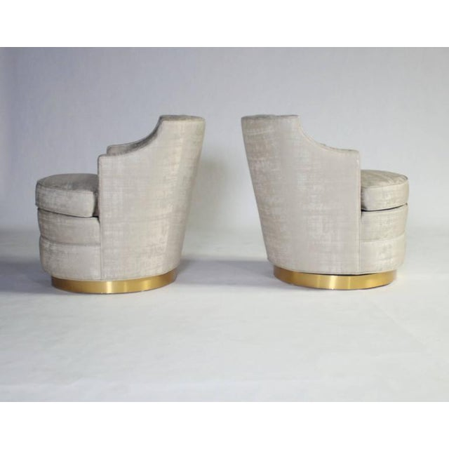 Lovely pair of swivel chairs by Edward Wormley for Dunbar reupholstered in a champagne color fabric with a subtle silvery...