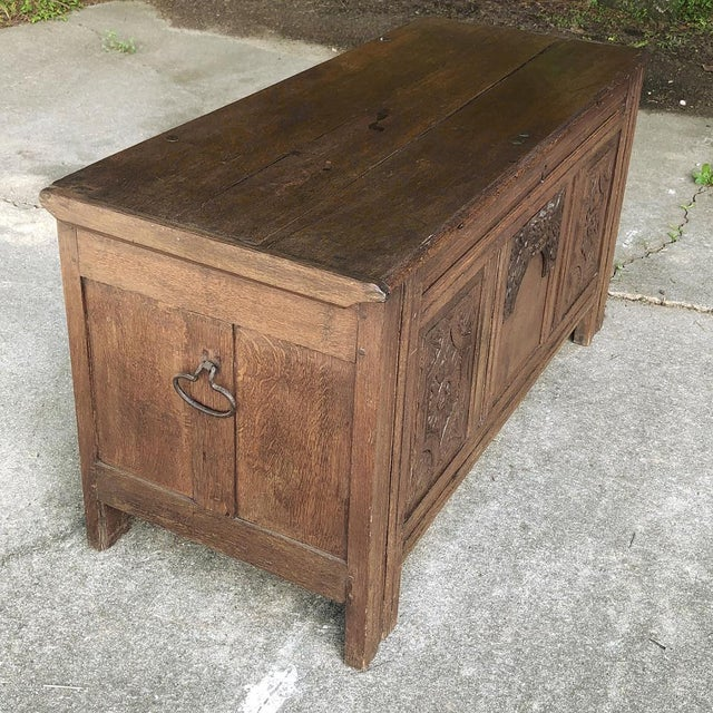 Early 19th Century Country French Rustic Oak Trunk features charming hand-carved embellishment on the front, forged iron...