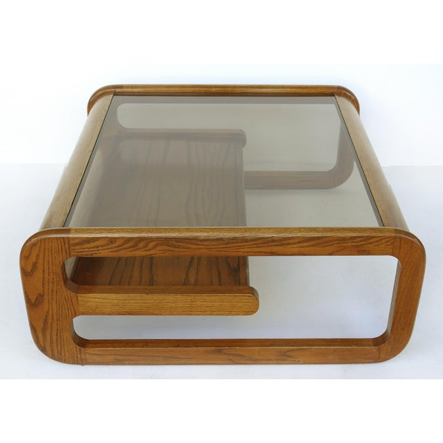 Offered for sale is a Lou Hodges (1937-2003) mid-century modern two-tiered California coffee table with inset glass top....