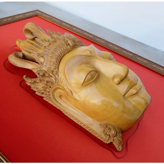 Large golden wood carved Thai Buddha head with ornate headdress, mounted on a matte red silk backing, with a carved wood...