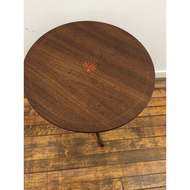 Round occasional table. American tilt top. Inlay center rosette and border trim. Has character consistent with age.